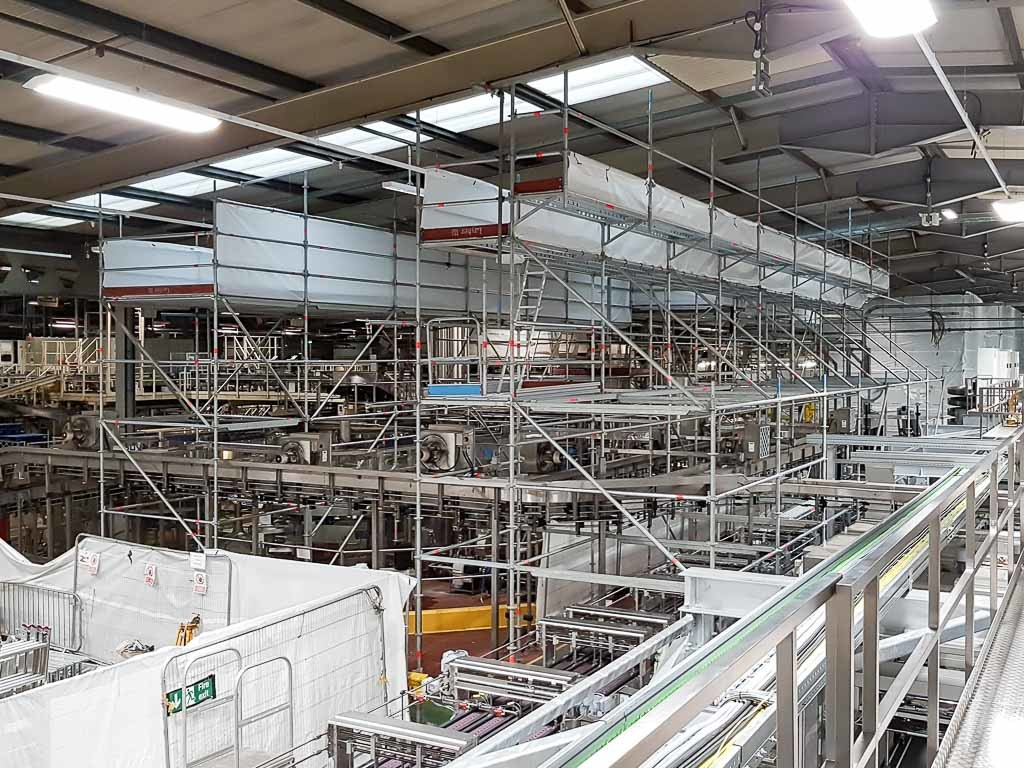 Industrial scaffolding with dust containment over food and drink factory conveyors
